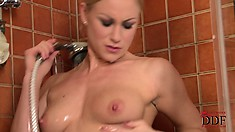 Blonde is in the shower and poses before sitting on the floor to rub
